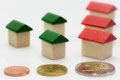 Monedas junto a casas en miniatura